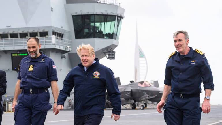From left, Commodore Steve Moorhouse, U.K. Prime Minister Boris Johnson and First Sea Lord Admiral Tony Radakin walk on the flight deck during a visit to HMS Queen Elizabeth aircraft carrier on May 21